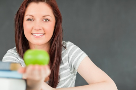 Beautilful young woman showing an apple with the camera focus on the model in a classroom photo