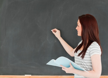 Young woman writting on a blackboard holding her notes in a classroom Stock Photo - 10074498