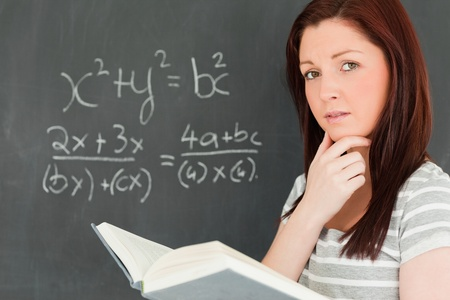 Reflective young woman trying to solve an equation in a classroom Stock Photo - 10074694