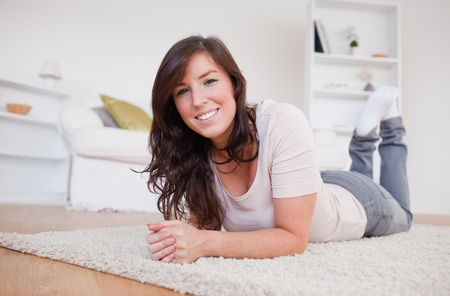 Beautiful brunette woman posing while lying on a carpet in the living room Stock Photo - 10074134