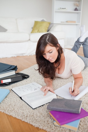 Young pretty woman writing on a notebook while lying on a carpet in the living room photo