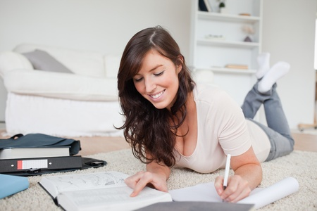 Young cute woman writing on a notebook while lying on a carpet in the living room photo