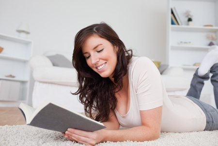 Young cute woman reading a book while lying on a carpet in the living room photo