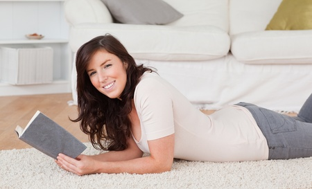 Young charming woman reading a book while lying on a carpet in the living room photo
