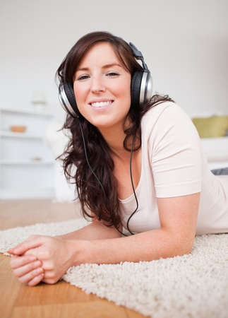 Beautiful brunette female using headphones while lying on a carpet in the living room Stock Photo - 10073061