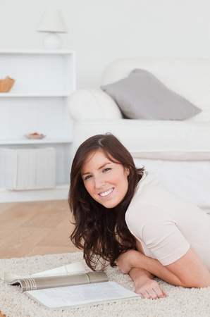 Young good looking woman reading a magazine while lying on a carpet in the living room Stock Photo - 10071418