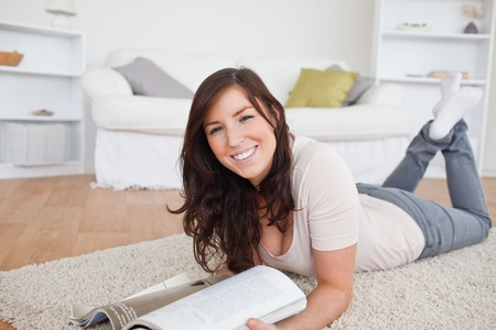 Good looking woman reading a magazine while lying on a carpet in the living room photo