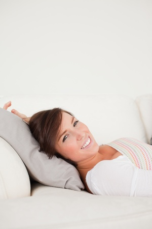 Cute brunette woman posing while lying on a sofa in the living room Stock Photo - 10070754