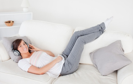 Attractive brunette female relaxing with her headphones while lying on a sofa in the living room Stock Photo - 10069778