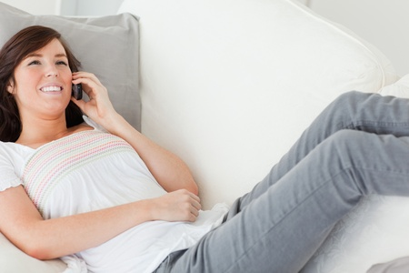 Good looking brunette female on the phone while lying on a sofa in the living room photo