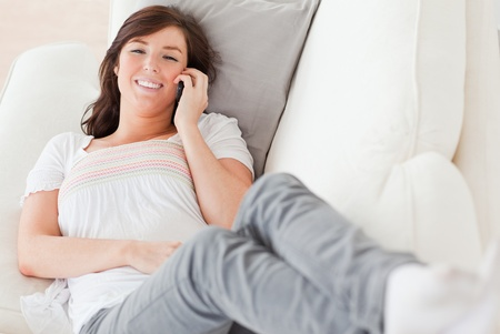 Cute brunette female on the phone while lying on a sofa in the living room photo