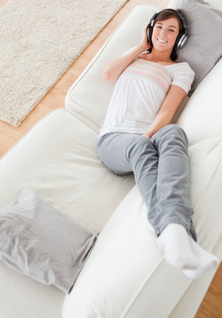 Charming brunette female relaxing with her headphones while lying on a sofa in the living room photo