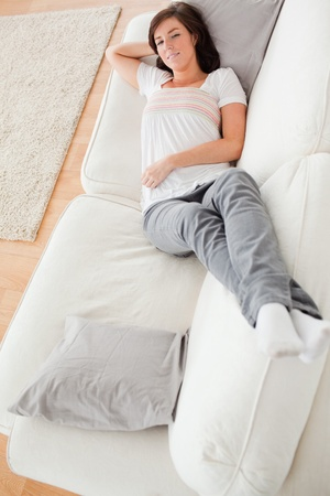 Young beautiful female having a rest while lying on a sofa in the living room photo