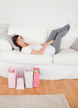 Young charming female posing with her shopping bags while lying on a sofa in the living room photo