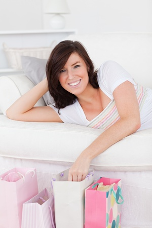 Young pretty female posing with her shopping bags while lying on a sofa in the living room photo