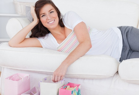 Young attractive woman posing with her shopping bags while lying on a sofa in the living room Stock Photo - 10071832