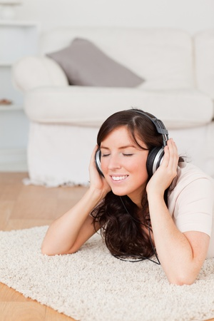 Good looking brunette woman using headphones while lying on a carpet in the living room photo