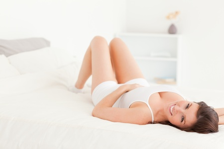 Charming brunette woman posing while lying on a bed photo
