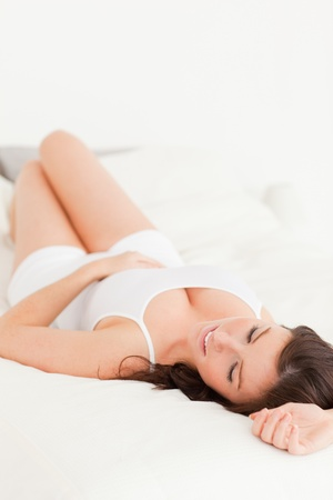 Lovely brunette woman posing while lying on a bed photo