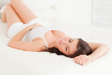 Cute brunette woman posing while lying on a bed Stock Photo - 10070823