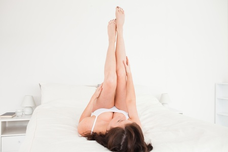 Good looking brunette female stretching her legs while lying on a bed photo