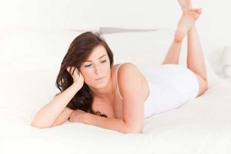 Charming brunette female posing while lying on a bed photo