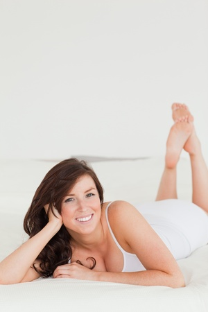 Lovely brunette female posing while lying on a bed photo