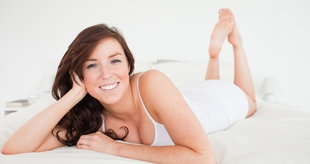 Smiling brunette female posing while lying on a bed Stock Photo - 10070764