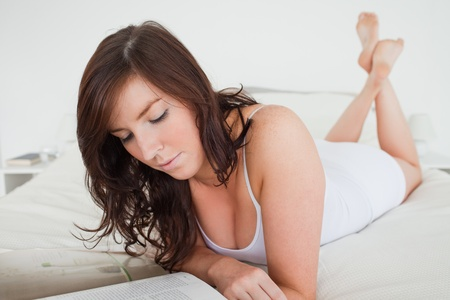 Good looking female reading a magazine while lying on a bed photo