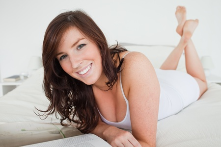 Attractive female reading a magazine while lying on a bed photo
