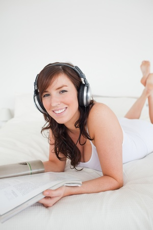 Beautiful female with headphones reading a magazine while lying on a bed photo