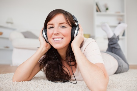 Glad brunette woman using headphones while lying on a carpet in the living room photo