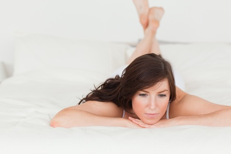 Cute brunette female posing while lying on a bed Stock Photo - 10070969