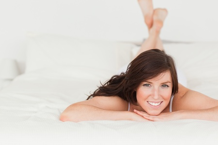Good looking brunette female posing while lying on a bed photo
