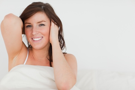 Charming brunette woman awaking while sitting on a bed photo
