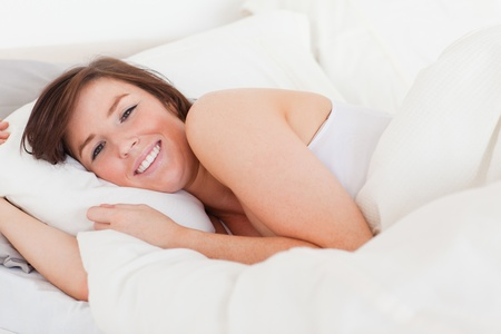 Beautiful brunette female posing while lying on a bed Stock Photo - 10071805