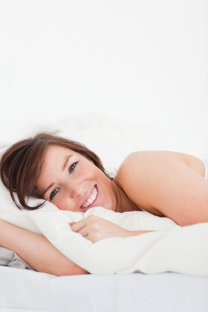 Pretty brunette female posing while lying on a bed photo