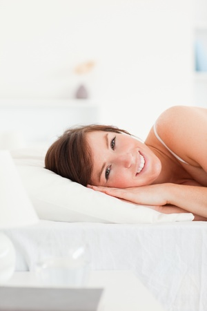 Cute brunette female posing while lying on a bed photo