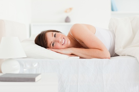 Lovely brunette female posing while lying on a bed Stock Photo - 10070315
