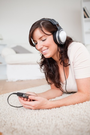 Pretty brunette woman listening to music with her mp3 player while lying on a carpet in the living room photo