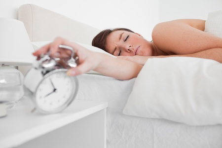 Beautiful brunette female awaking with a clock while lying on a bed Stock Photo - 10070998