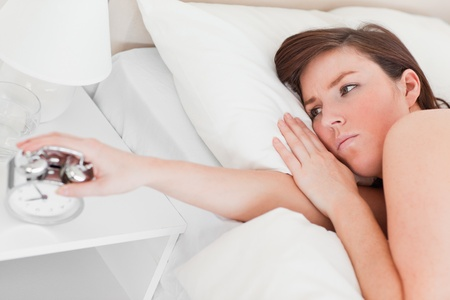 awaking: Lovely brunette female awaking with a clock while lying on a bed