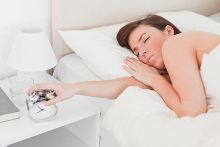 Pretty brunette female awaking with a clock while lying on a bed photo