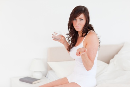 Lovely brunette female taking some pills while sitting on a bed Stock Photo - 10070140
