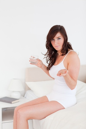 Cute brunette female taking some pills while sitting on a bed photo