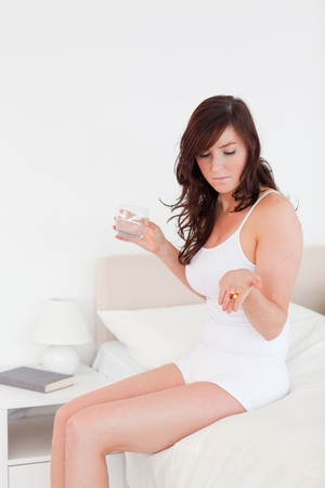Beautiful brunette woman taking some pills while sitting on a bed photo