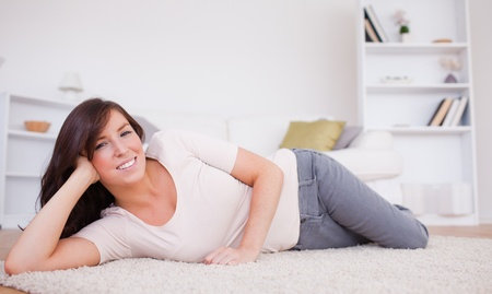 Gorgeous brunette woman posing while lying on a carpet in the living room Stock Photo - 10070184