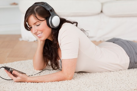 Gorgeous brunette female listening to music with her mp3 player while lying on a carpet in the living room photo