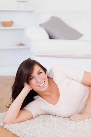 Charming brunette woman posing while lying on a carpet in the living room Stock Photo - 10072254