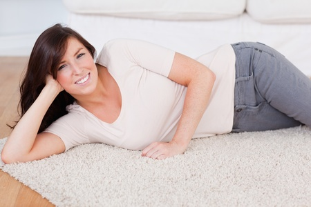 Beautiful smiling woman posing while lying on a carpet in the living room photo